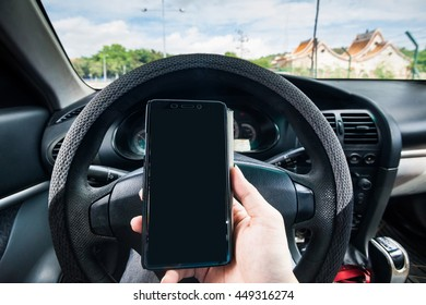 Hand holding a cellphone while driving indicating danger of text and drive