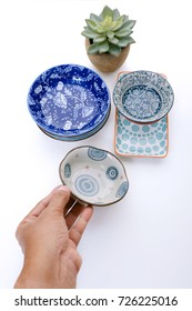 Hand holding ceramic plate over white table