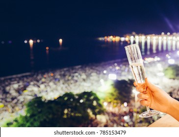 Hand holding champagne glass overlooking Copacabana Beach in Rio de Janeiro, Brazil at New Years Eve