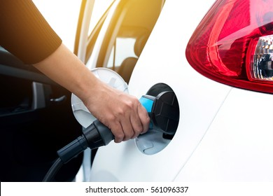 Hand holding and charging electric car with the power cable supply plugged in . Flare light effect