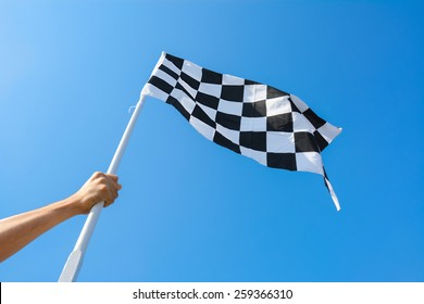 Hand holding checkered flag on blue sky background