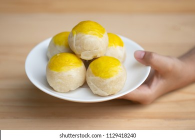 Hand holding Chinese pastry moon cake roll ball, made of wafer stuffed, mung bean, and salted egg yolk. Thai people call this is Kanom Pia. Soft focus and blur.