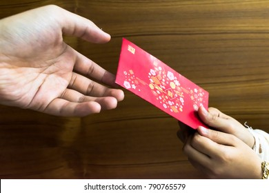 """Hand holding Chinese red envelopes known as """"ang pau"""" with word """"Gong Xi Fa Cai"""" written in Mandarin. Gong Xi Fa Cai means wishing you to be prosperous in the coming year. Happy Chinese New Year!"""
