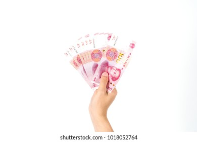 Hand holding Chinese yuan banknotes on white background. Close up human hand giving and paying China money (rmb or renminbi)
