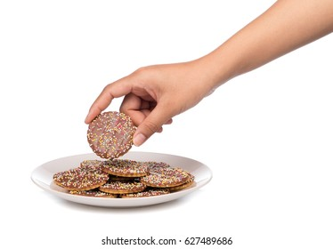 hand holding chocolate cookies sprinkle on dish isolated on white background.