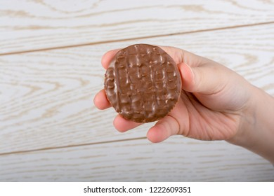 Hand holding a chocolate covered cookie on a wooden background
