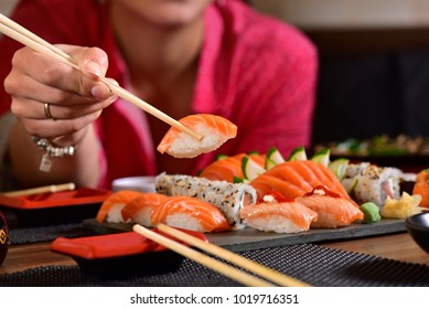 Hand holding a chopstick with nigiri sushi on restaurant table