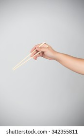 Hand holding chopsticks, isolated on white background.