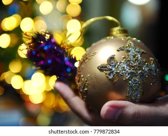Hand holding Christmas ball on beautiful bokeh light background. Holiday best wishes concept image for Christmas and New Year 2018. (selective focus, space for text)