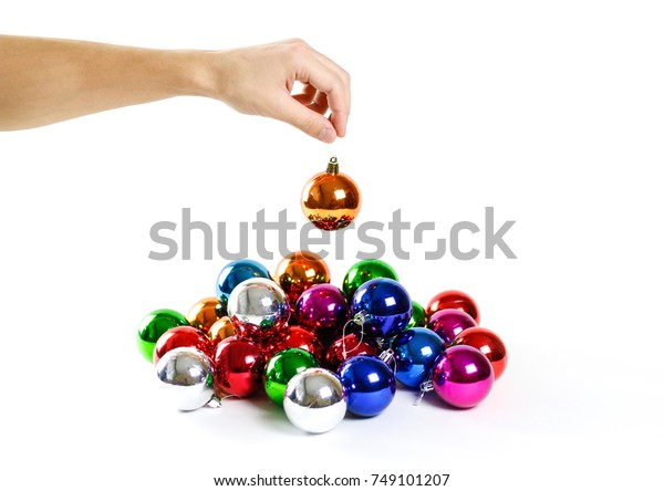 Hand holding Christmas ball. On the background of many Christmas balls. Lot Christmas tree decorations. Colored glass balls. Isolated on a white background