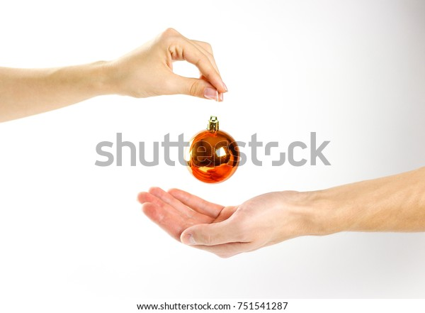Hand holding Christmas ball. On the background of many Christmas balls. Lot Christmas tree decorations. Colored glass balls. Isolated on a white background.