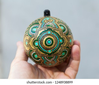Hand holding christmas decoration ball on light background.
