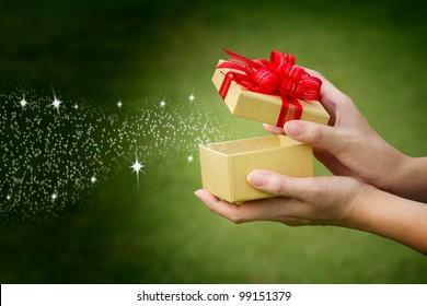 hand holding christmas gift box, xmas present box,  hand open xmas red ribbon bow gold christmas present; joyeux noel, feliz navidad, merry christmas, boxing day, xmas sale, happy birthday concept