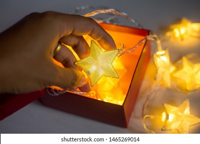 Hand holding christmas lamp star on white background