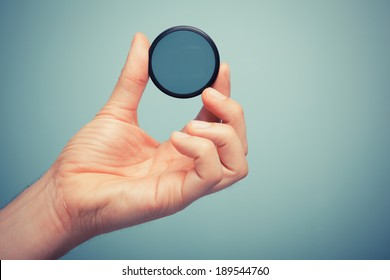 A hand is holding circular polarizer filter