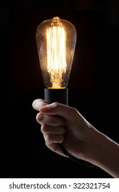 Hand holding classic Edison light bulb on black background with space for text
