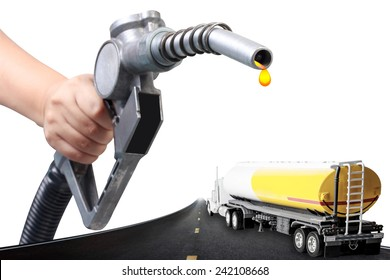 Hand holding a classic fuel nozzle pumping and truck with fuel tank on the highway