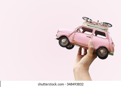 Hand holding classic mini model with bicycle, Travel concept