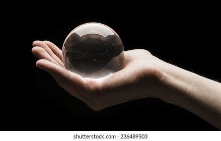 Hand holding a clear transparent crystal glass ball in their palm isolated on black background