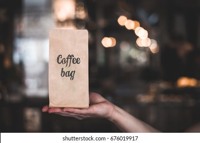 Hand holding coffee bag with inscription COFFEE BAG on blured background