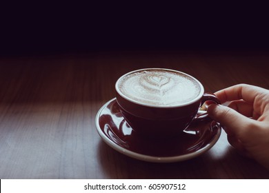 Hand holding coffee cup in coffee cafe shop.