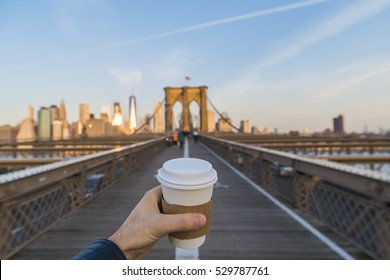 Hand holding coffee cup in New York City.