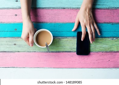 hand holding coffee cup and using smart phone