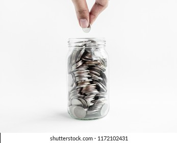 Hand holding coin in glass jar isolated on white background. Saving money concept.