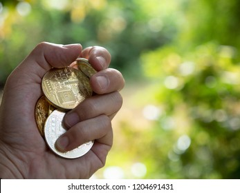 hand holding coin with nature bokeh background and copy space, cryptocurrency money exchange investment concept.
