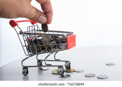 A hand holding a coin to put in to mini trolley with full of coins inside. saving