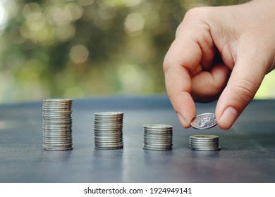 hand holding coin and stack of money on table, saving and manage to success business, e-commerce and shopping online technology, economic crisis risk and problem concept