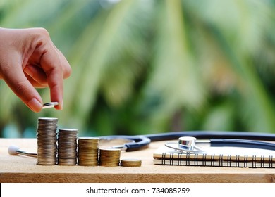 hand holding coin, stack of money, stethoscope and notebook on wood table, healthcare and business concept