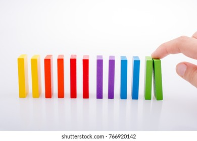 Hand holding color dominoes on a white background