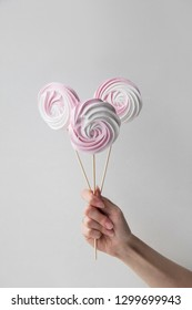 Hand holding colorful meringue lollipops on a stick, white background. Hand holding Candy Sweet dessert in white and pink twist for meringue. Vintage pastel colored French meringues.