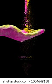Hand holding colorful powder for holi festival of colors. Closeup over a black background with copy space