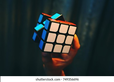 Hand holding colorful Rubik's cubes on dark background.Rubik's Cube was invented in 1974 by Hungarian sculptor and professor of architecture Erno Rubik.
