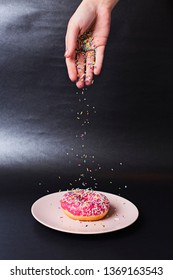 Hand holding colorful sprinkles is decorating a pink frosted sugar bomb doughnut, placed on a shiny black background. Studio shot