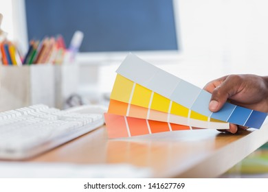 Hand holding colour charts in a modern office closeup