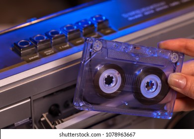 Hand holding compact audio cassette tape, about to insert it in old music player - closeup
