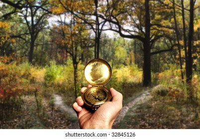 hand holding a compass in front of a choice between two paths in the wood