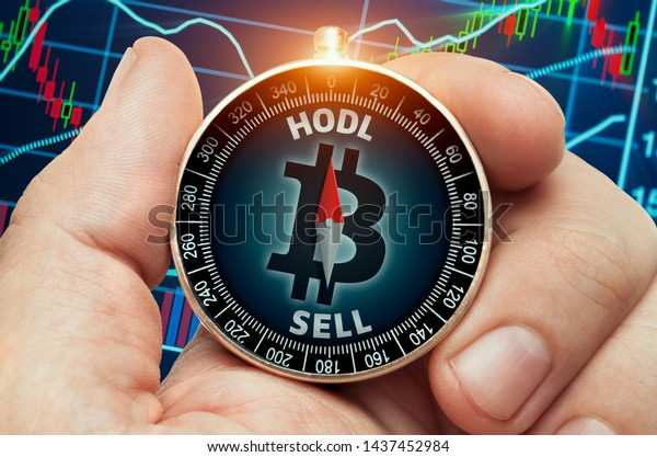 hand holding compass with glowing bitcoin symbol in front of stock market chart data. Compass needle showing HODL word.