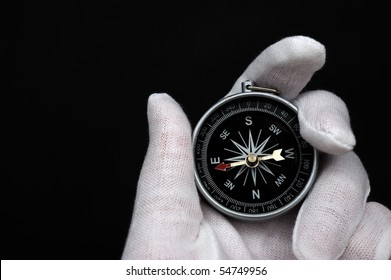 Hand holding the compass isolated on black background.