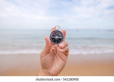 Hand holding a compass on the beach