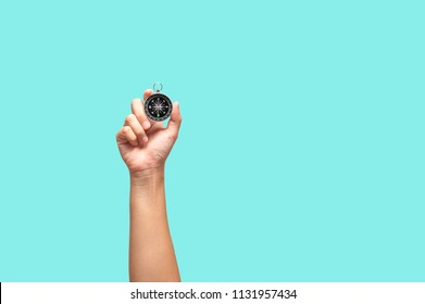 Hand holding compass in one hand  on green background, Concepts of searching direction with compass.