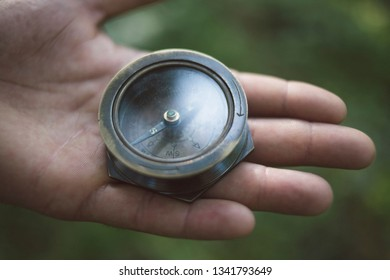 Hand holding a compass outdoors in the nature