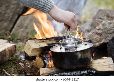 Hand Holding Cooking Pot Over Bonfire