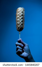 hand holding corn dog on blue color background, scary mood for unhealthy diet junk food