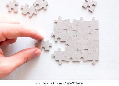 hand holding the correct part of the puzzle on a white background