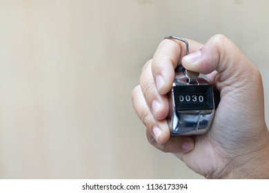 Hand holding a counter tally. Counting people.