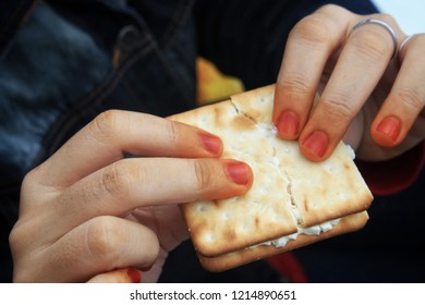 Hand holding crackers.